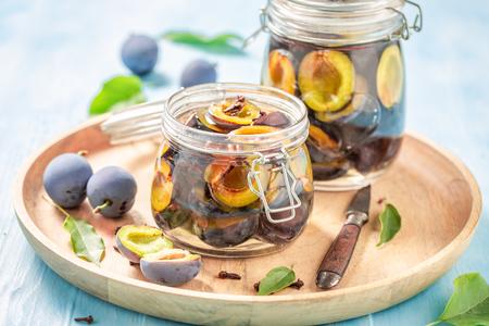 Tasty pickled purple plums in the jar Banco de Imagens - 107639721