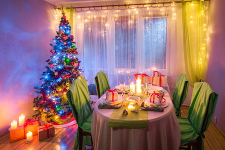 Colorful Christmas table setting with gifts and gingerbread