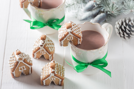 Gingerbread cottages with hot cocoa for Christmas on white table Stock Photo