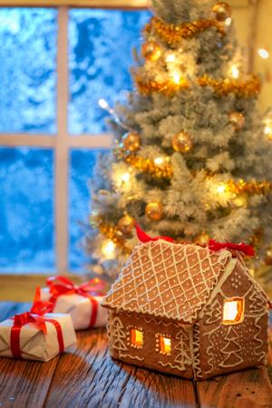 Weihnachtsbaum und Geschenke mit gefrorenem Fenster und Licht