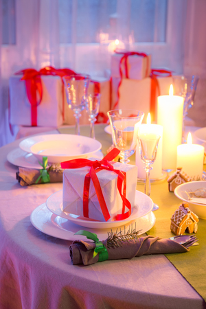 Closeup of Christmas table setting with gifts and candles Stock Photo