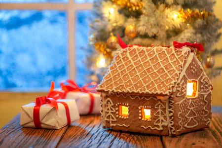 Schöne Geschenke und Weihnachtsbaum mit gefrorenem Fenster und Licht Standard-Bild