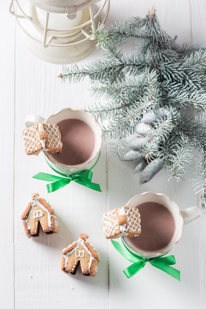 Homemade gingerbread cottages with cocoa for Christmas on white table