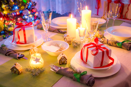 Christmas table setting with candles and gifts