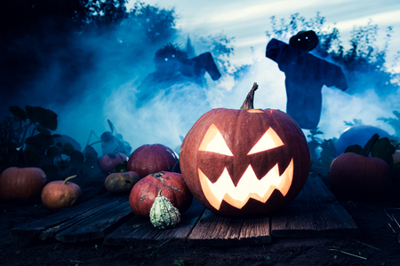 Orange pumpkin with scarecrows and blue mist for Halloween