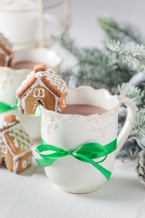 Closeup of gingerbread with hot cocoa for Christmas on white