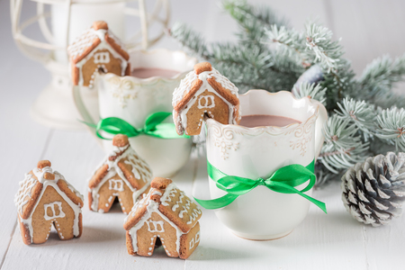 Small and sweet gingerbread cottages with hot drink for Christmas