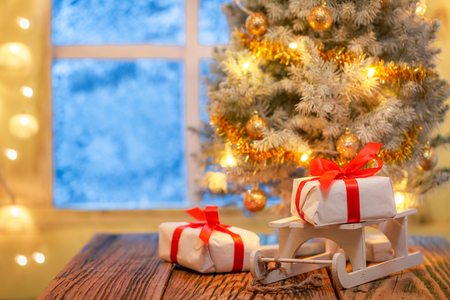 Beautiful Christmas tree and gifts with frozen window and light Stock Photo