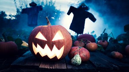 Scary orange Halloween pumpkin on dark field with scarecrows Stockfoto