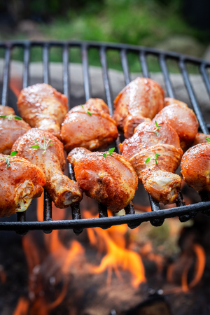 Delicious chicken leg on grill with herbs and spices