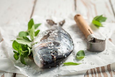 Preparing whole sea bream with lime and mint leaves