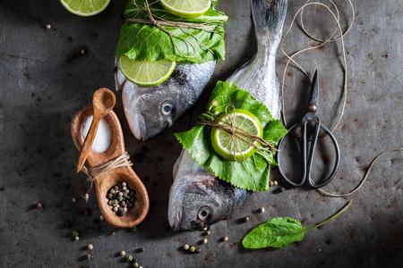 Seasoning whole fish with horseradish and lemon Stock Photo