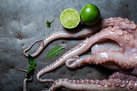 Preparing fresh octopus with lime and mint leaves Imagens