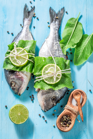 Seasoning whole fish with lime and horseradish leaves