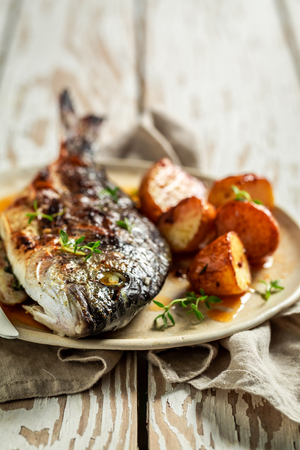 Tasty potatoes and seabream with herbs and tomatoes