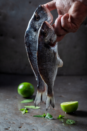 Freshly caught two bream with lime holding in hand