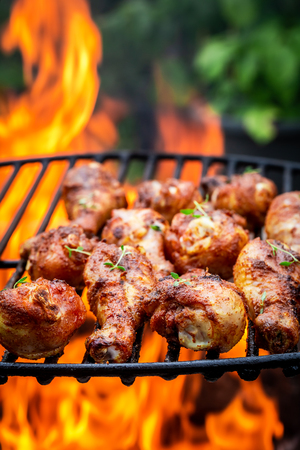 Tasty chicken leg on grill with flames