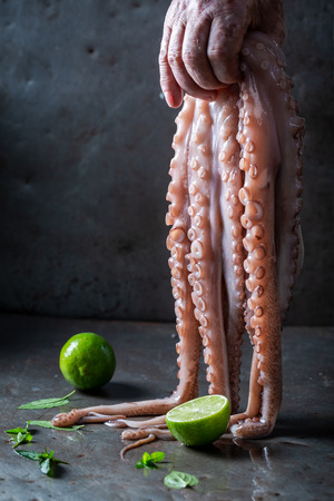 Freshly caught octopus holding in hand and lime