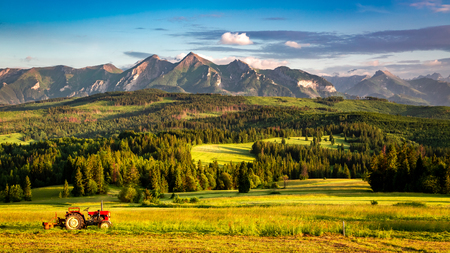 Breathtaking sunset at Belianske Tatra mountains with tractor in Poland