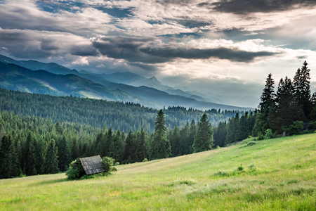 Beautiful small cottage on green valley at sunset, Tatra mountains
