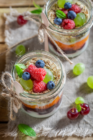Tasty oat flakes with fresh fruits and yogurt in jar Stock Photo