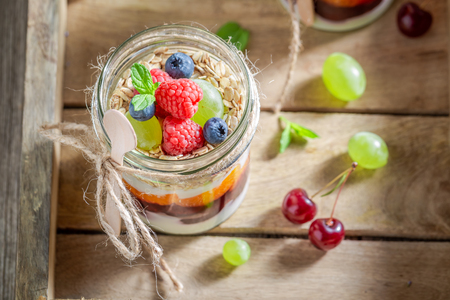 Delicious granola with fresh fruits and yogurt in jar