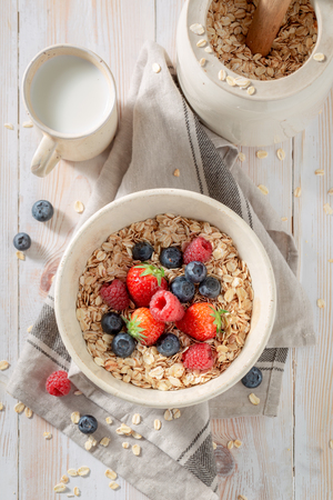 Tasty oat flakes with fruits for breakfast on rustic table