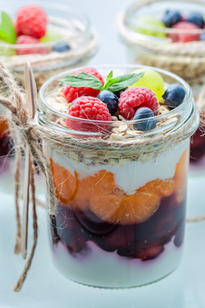 Granola in jar with yogurt and berry fruits on white