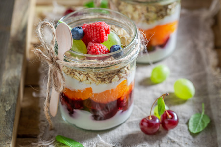 Healthy oat flakes with fresh fruits and yoghurt in jar Stock Photo - 109412747