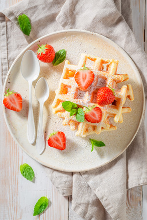 Delicious wafers with powdered sugar and fruits