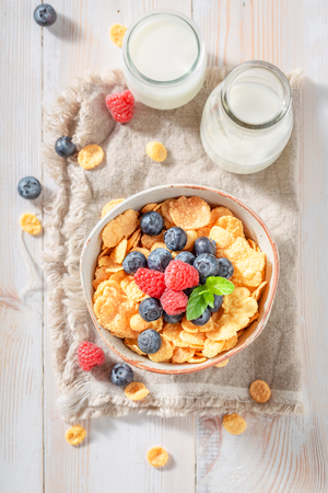 Healthy cornflakes with berry fruits and milk for breakfast