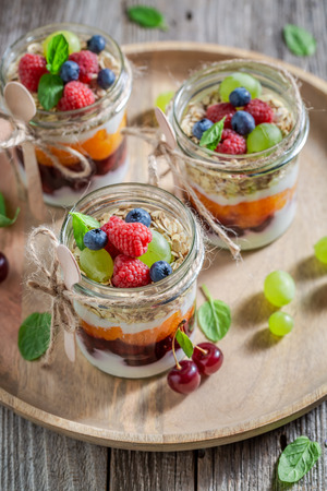 Healthy granola in jar with yogurt and berry fruits