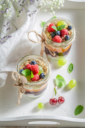 Homemade oat flakes in jar with yogurt and berry fruits Stock Photo