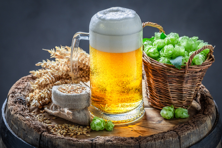 Gold pint of beer on wooden barrel