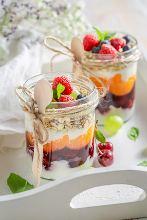 Delicious oat flakes in jar with yogurt and berry fruits