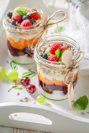 Healthy oat flakes in jar with yogurt and berry fruits Stock Photo