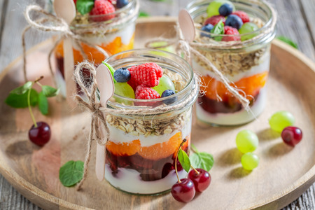 Sweet oat flakes in jar with yogurt and berry fruits