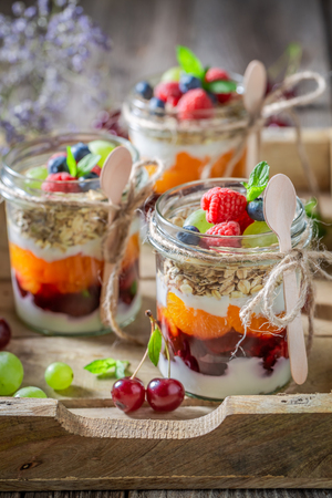 Sweet granola in jar with yogurt and berry fruits