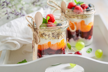 Fresh granola in jar with yogurt and berry fruits Stock Photo