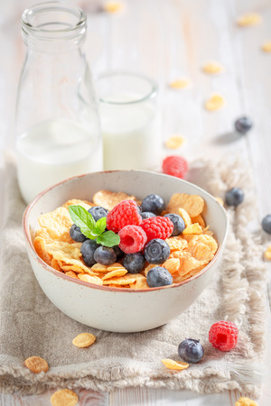 Sweet cornflakes with berry fruits and milk on rustic table
