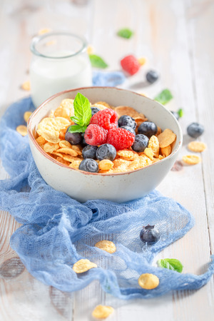 Sweet cornflakes with berry fruits and milk for breakfast Imagens