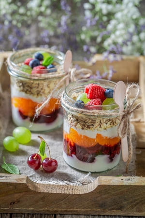 Delicious oat flakes with fresh fruits and yogurt in jar