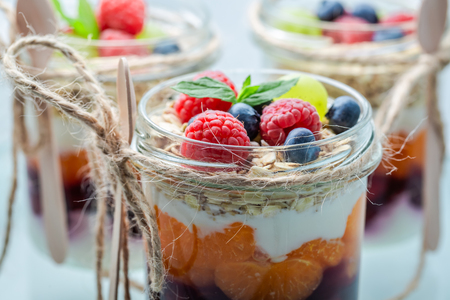 Granola in jar with berry fruits and yogurt on white