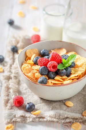 Healthy cornflakes with berry fruits and milk on rustic table