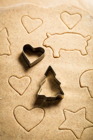 Cutting christmas gingerbread cookies before baking for Christmas