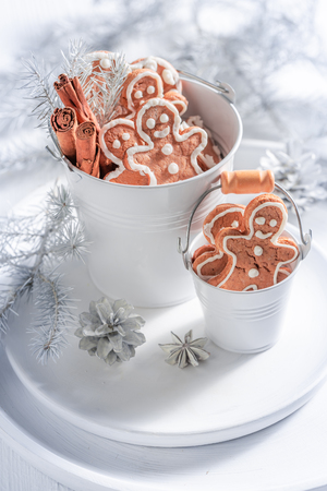 Homemade gingerbread man for Christmas in white bucket