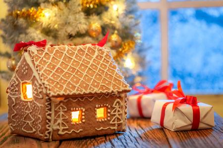 Lebkuchenhaus, Geschenke und Weihnachtsbaum mit gefrorenem Fenster