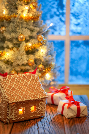 Gingerbread cottage, Christmas tree and presents with blue frozen window