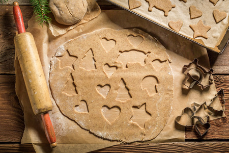 Cutting gingerbread cookies for Christmas on old rustic table