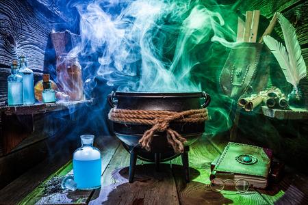 Caldero de brujo con pociones mágicas y libros para Halloween Foto de archivo
